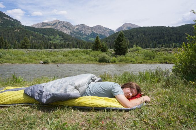 The man is resting in a sleeping bag