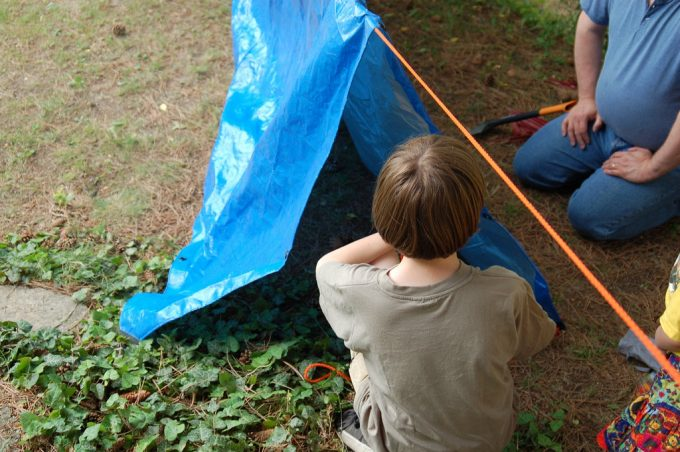 kid and dad making tarp tent