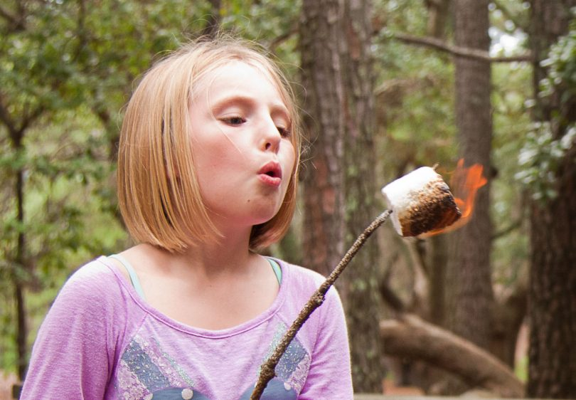 kid blows on a roasted marshmallow