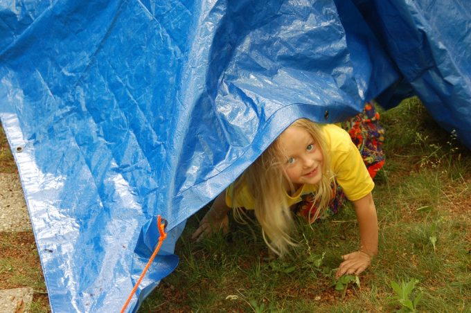 little girl under tarp tent