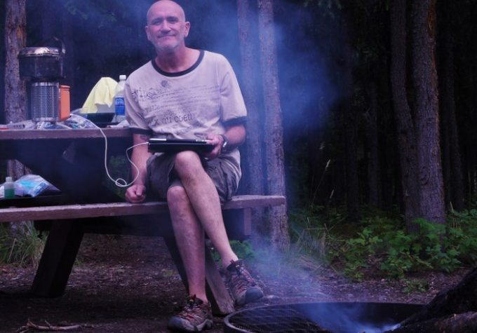 man sitting and using biolite stove