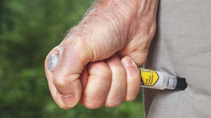 man using and Epipen