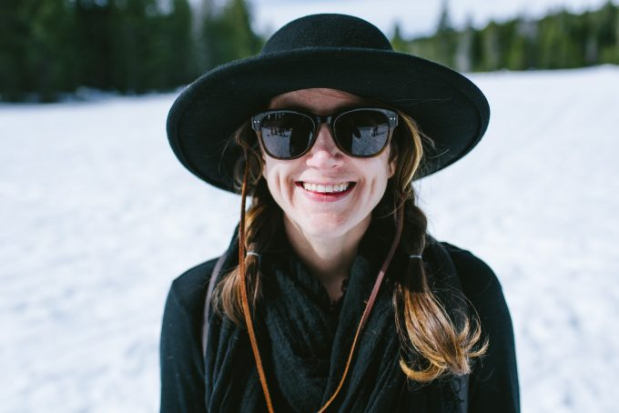 smiling woman with hat and sunglasses on the snow