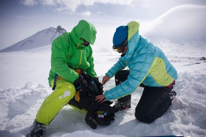 two hikers packing a tent on the snow