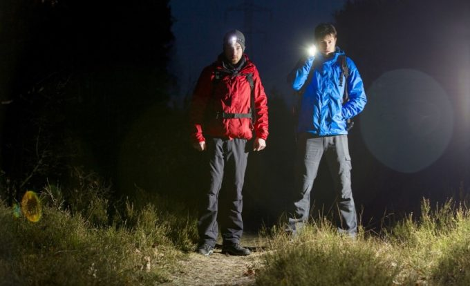 two night hikers with flashlight