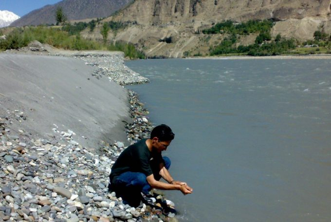 man washing hands in river