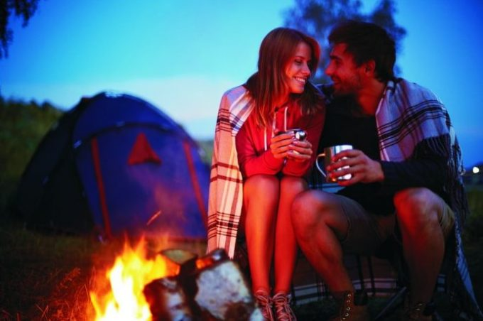 couple smiling near campfire