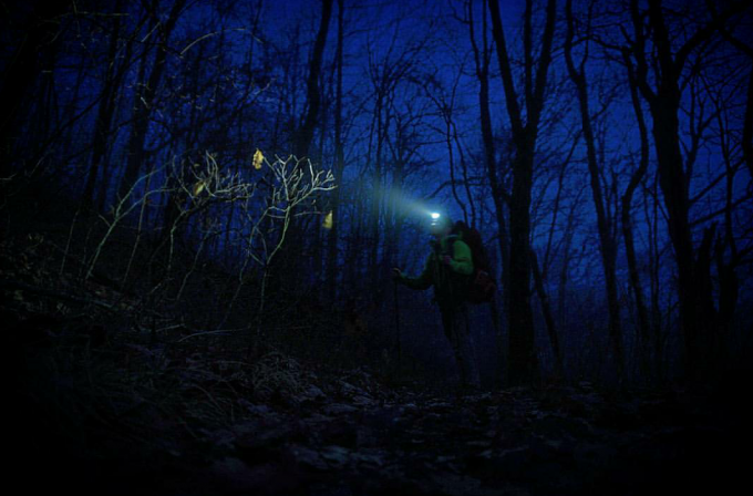 hiker alone in the woods at night