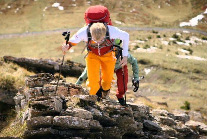 climbing on rocks with trekking poles