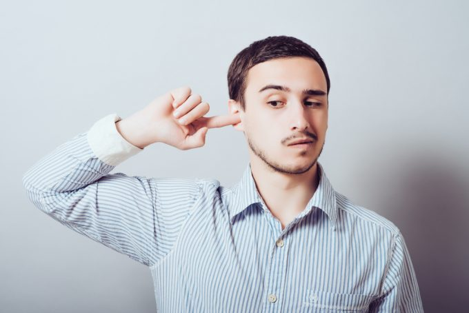 man with finger in his ear