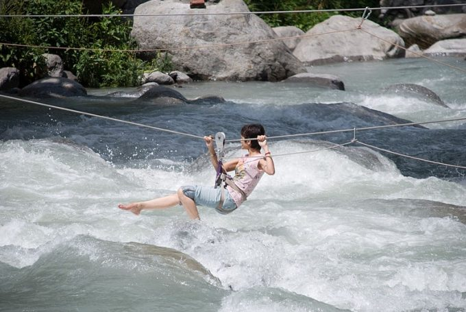 woman crossing river with zip line