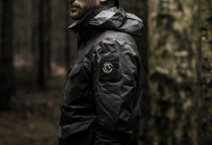 Man is Wearing Tactical Jacket in the Woods